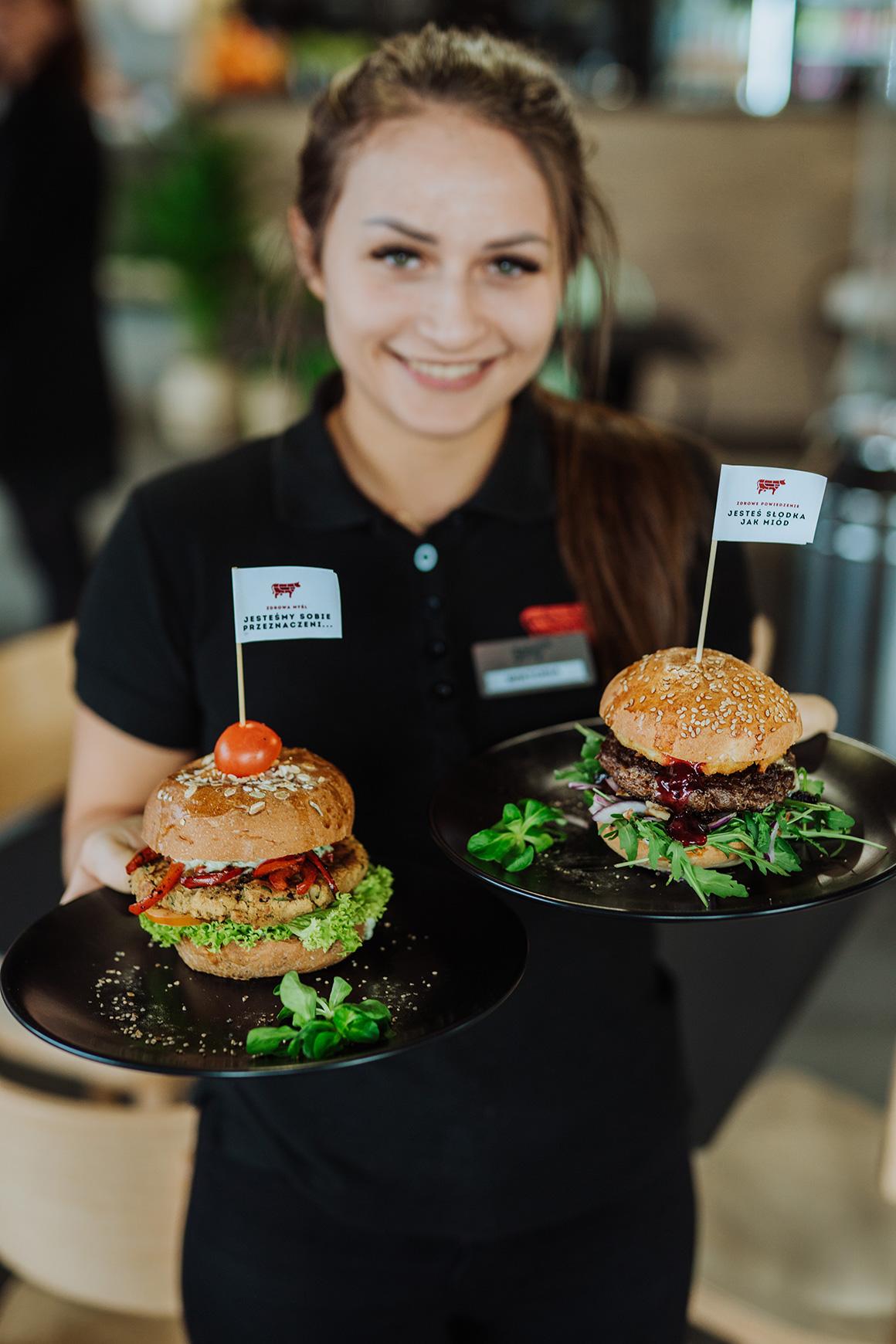 Pracownica zdrowej krowy z burgerami - Zdrowa Krowa